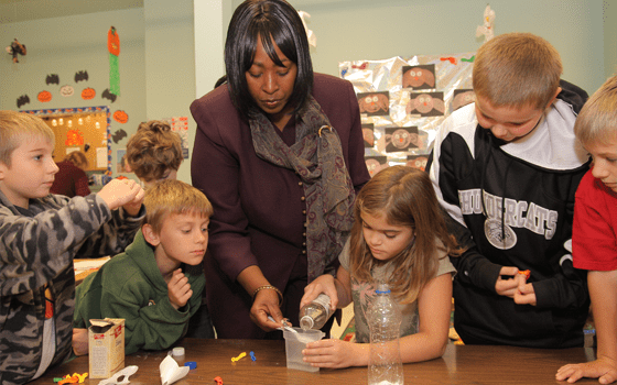 Backpackers Image, shows a teacher participating in an crafting activity with a group of students.