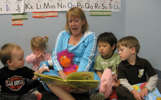 Preschool Advantage Image, teacher reading a book to 4 of her young students.