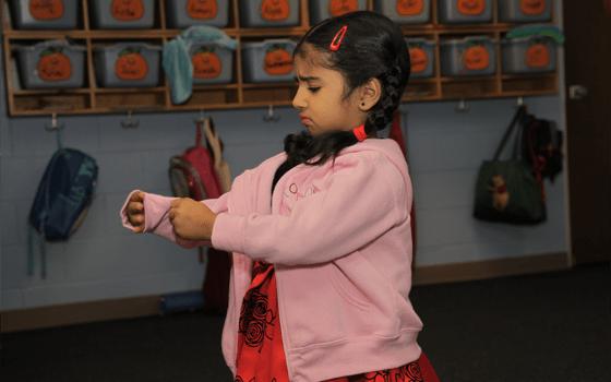 Preschool Advantage Plus Image, child putting on a coat.