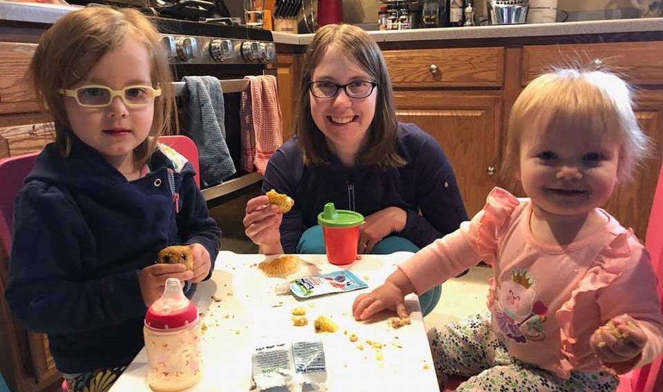 Mother eating muffins with her daughters