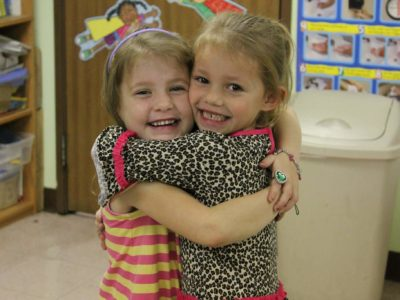 Two Young Female Students Hugging and Smiling